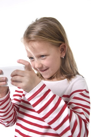 cell phone addiction: close up candid portrait of beautiful female child with blond hair and blue eyes using mobile phone playing game excited isolated on white background in children internet gaming addiction concept