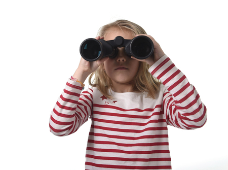 observing: blond hair young little girl looking holding binoculars looking through observing and watching curious isolated on white background