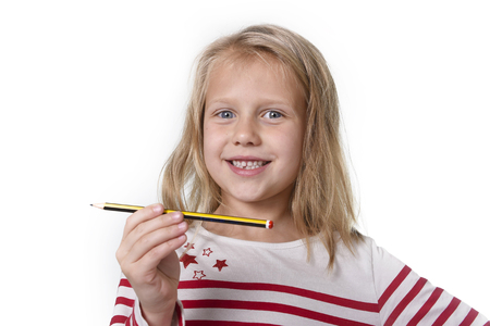 junior education: sweet beautiful female child 6 to 8 years old with cute blonde hair and blue eyes holding pencil isolated on white background in education and primary or junior school supplies concept