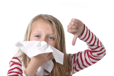 8 years old: 7 or 8 years old sweet and cute blond hair little girl blowing her nose with paper tissue having a cold feeling sick in child winter flu health care concept isolated on white background Stock Photo