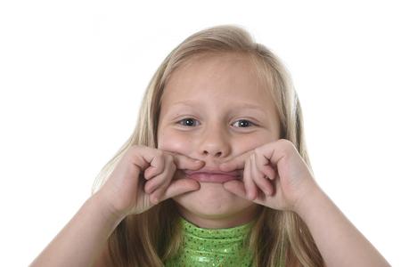 rubia ojos azules: niña de 6 o 7 años de edad con el pelo rubio y los ojos azules que sonríe feliz posando aisladas sobre fondo blanco que muestra sus labios en clase de lengua para la educación infantil y las partes del cuerpo diagrama de la escuela serie