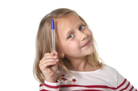 junior education: sweet beautiful female child 6 to 8 years old with cute blonde hair and blue eyes holding ball pen isolated on white background in education and primary or junior school supplies concept