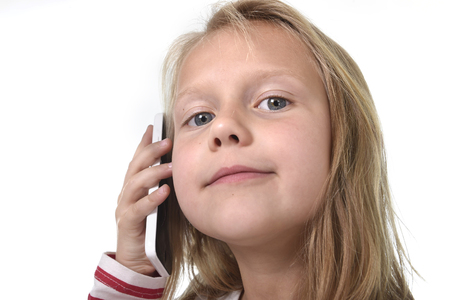 cell phone addiction: close up candid portrait of beautiful female child with blond hair and blue eyes using mobile phone talking happy and playful isolated on white background in children smartphone addiction concept