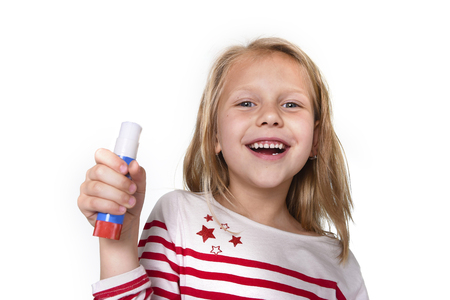 sweet beautiful female child 6 to 8 years old with cute blonde hair and blue eyes holding glue stick isolated on white background in education and primary or junior school supplies concept Imagens
