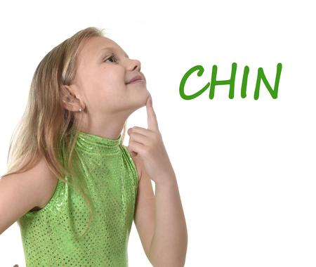 blonde yeux bleus: 6 ou 7 ans petite fille aux cheveux blonds et yeux bleus souriant heureux posant isolé sur fond blanc menton pointant dans l'apprentissage de la langue anglaise l'éducation scolaire carte des parties du corps ensemble