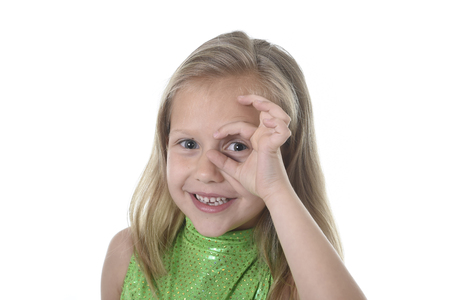 6 or 7 years old little girl with blond hair and blue eyes smiling happy posing isolated on white background circling eye in language lesson for child education and body parts school chart serie Stock Photo
