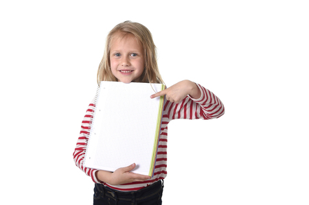 8 years old: sweet beautiful female child 6 to 8 years old with cute blonde hair and blue eyes holding notebook or notepad isolated on white in education and primary or junior school supplies concept