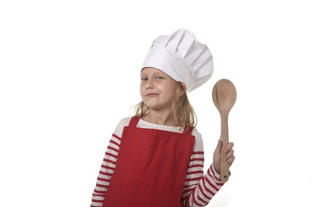 playing with spoon: 6 or 7 years old little girl in cooking hat and red apron playing cook smiling  happy holding spoon isolated on white background looking excited