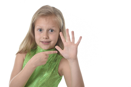 six girl: 6 or 7 years old little girl with blond hair and blue eyes smiling happy posing isolated on white background pointing hand in language lesson for child education and body parts school chart serie Stock Photo