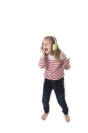 7 years old: sweet little girl 7 years old with blonde hair and closed eyes listening to music with headphones and mobile phone singing and dancing happy and excited  isolated on white background Stock Photo