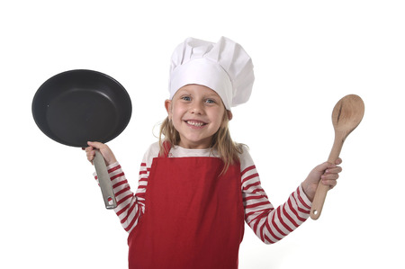 6 7 years: 6 or 7 years old little girl in cooking hat and red apron playing cook smiling  happy holding pan and spoon isolated on white background looking excited