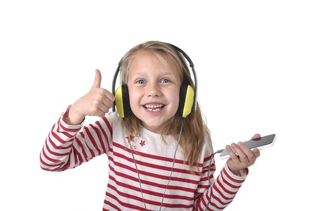 7 years old: sweet little girl 7 years old with blonde hair and blue eyes listening to music with headphones and mobile phone giving thumb up enjoying song happy isolated on white background