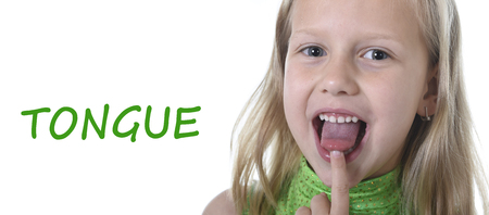 idiomas: niña de 6 o 7 años de edad con el pelo rubio y los ojos azules que sonríe feliz posando aisladas sobre fondo blanco que señala la lengua en el aprendizaje de Inglés idioma ajustado educación tarjeta de partes del cuerpo de la escuela