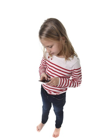 cell phone addiction: candid portrait of beautiful female child with blond hair and blue eyes using mobile phone playing game excited isolated on white background in children internet gaming addiction concept