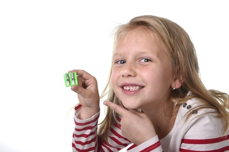 junior education: sweet beautiful female child 6 to 8 years old with cute blonde hair and blue eyes holding drawing pencil sharpener isolated on white in education and primary or junior school supplies concept