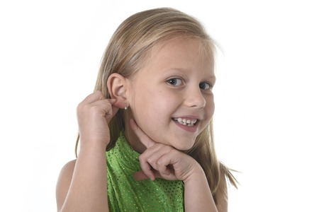 6 or 7 years old little girl with blond hair and blue eyes smiling happy posing isolated on white background pointing ear in language lesson for child education and body parts school chart serie