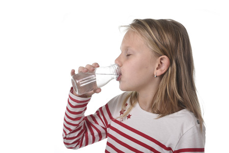 6 7 years: cute sweet little girl with blue eyes and blond hair 6 or 7 years old holding bottle of water drinking isolated on white background