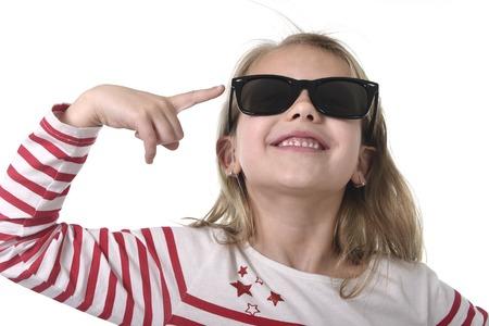 niños rubios: hermosa 6 a 8 años de edad niña con el pelo rubio llevaba suéter de rayas rojo y grandes gafas de sol apuntando con su dedo feliz y juguetón aislado en el fondo blanco