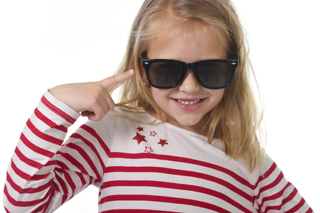 8 years old: beautiful 6 to 8 years old female child with blond hair wearing red stripes sweater and big sunglasses pointing with her finger happy and playful isolated on white background