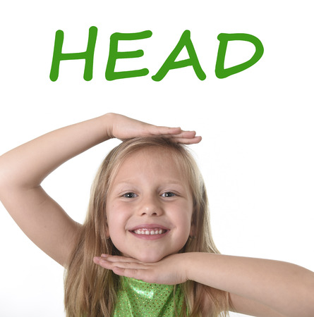 body parts: 6 or 7 years old little girl with blond hair and blue eyes smiling happy posing isolated on white background showing head in learning English language school education body parts card set