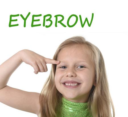 blonde yeux bleus: 6 ou 7 ans petite fille aux cheveux blonds et yeux bleus souriant heureux posant isolé sur fond blanc sourcil pointant dans l'apprentissage de la langue anglaise l'éducation scolaire carte des parties du corps ensemble