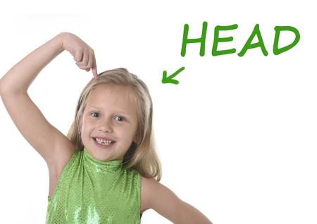 rubia ojos azules: niña de 6 o 7 años de edad con el pelo rubio y los ojos azules que sonríe feliz posando aisladas sobre fondo blanco cabeza apuntando en el aprendizaje de Inglés idioma ajustado educación tarjeta de partes del cuerpo de la escuela