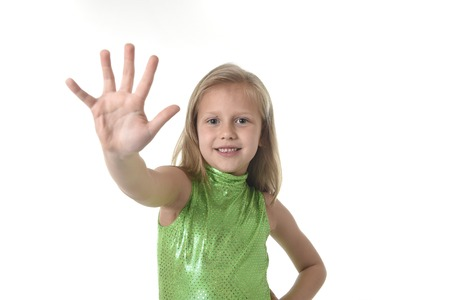 7 years old: 6 or 7 years old little girl with blond hair and blue eyes smiling happy posing isolated on white background showing hand in language lesson for child education and body parts school chart serie Stock Photo