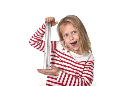 8 years old: sweet beautiful female child 6 to 8 years old with cute blonde hair and blue eyes holding ruler isolated on white background in education and primary or junior school supplies concept Stock Photo