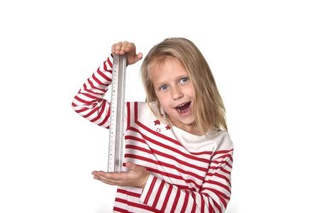 Zoet mooi vrouwelijk kind 6 tot 8 jaar oud met schattig blond haar en blauwe ogen houden liniaal geïsoleerd op witte achtergrond in het onderwijs en primaire of junior school levert concept Stockfoto