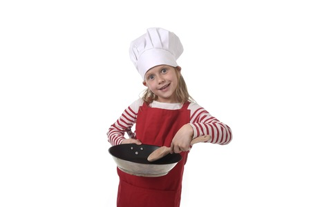 playing with spoon: 6 or 7 years old little girl in cooking hat and red apron playing cook smiling  happy holding pan and spoon isolated on white background looking excited