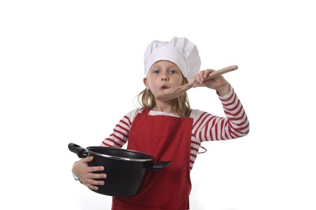 playing with spoon: 6 or 7 years old little girl in cooking hat and red apron playing cook smiling  happy holding pot and pretending tasting food with spoon isolated on white background looking excited