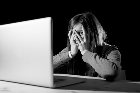 teenager girl suffering cyberbullying scared and depressed exposed to cyber bullying and internet harassment feeling sad and vulnerable in internet stalker danger and abuse problem