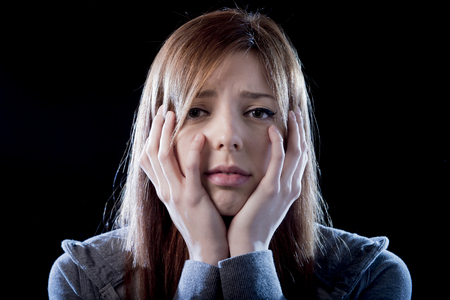 victim: young beautiful teenager girl with red hair feeling lonely and scared looking sad and desperate suffering depression as victim of cyber bullying or social abuse violence and rejection Stock Photo