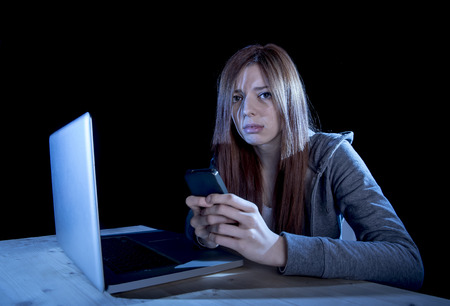cyber bullying: young scared and worried teenager girl using mobile phone and computer laptop as internet stalked victim abused and cyberbullying or cyber bullying stress concept in black background