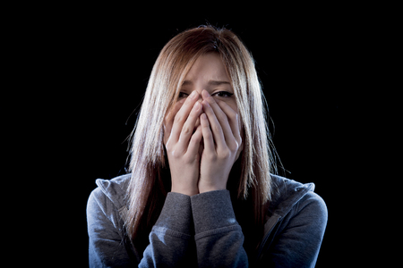 scared: young beautiful teenager girl with red hair feeling lonely and scared looking sad and desperate suffering depression as victim of cyber bullying or social abuse violence and rejection Stock Photo