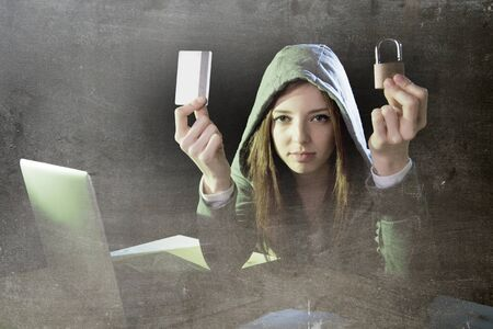 violating: young teenager hacker girl in hoodie holding credit card violating private password holding credit card and lock in cybercrime and cyber crime concept and internet information security concept