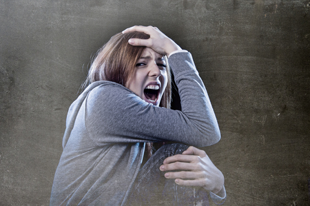 victim: young beautiful teenager girl with red hair feeling lonely screaming scared looking wasted desperate suffering depression as victim of cyber bullying or social abuse violence and rejection Stock Photo