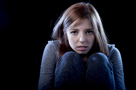 rejection sad: young beautiful teenager girl with red hair feeling lonely and scared looking sad and desperate suffering depression as victim of cyber bullying or social abuse violence and rejection Stock Photo