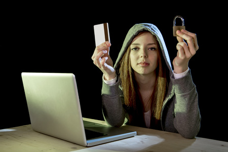 cybercrime: young teenager hacker girl in hoodie holding credit card violating private password holding credit card and lock in cybercrime and cyber crime concept and internet information security concept