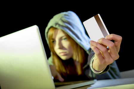violating: young teenager hacker girl in hoodie holding credit card violating private password holding credit card in cybercrime and cyber crime concept and internet information security concept Stock Photo