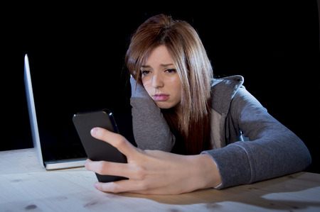 young scared and worried teenager girl using mobile phone and computer laptop as internet stalked victim abused and cyberbullying or cyber bullying stress concept in black background