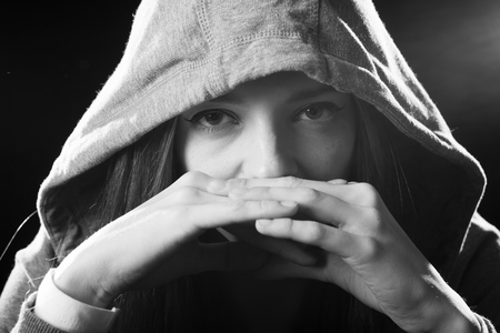defiant: close up portrait of cool teenager girl or young woman on her 20s posing cool showing attitude wearing hood on isolated on white background in modern hipster style looking defiant