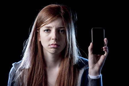 cyber woman: young scared and worried teenager girl holding mobile phone as internet stalked victim abused and cyberbullying or cyber bullying stress concept in black background