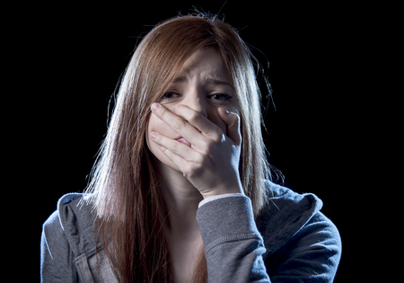 victim: lonely young teenager girl in stress and pain suffering depression looking sad and scared with fear face expression isolated on black background victim of abuse or in mental condition