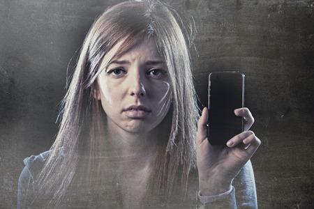 asustado: joven adolescente asustado y preocupado que sostiene el tel�fono m�vil como internet acosada v�ctima de abuso y acoso cibern�tico o cyberbullying concepto de la tensi�n en el fondo negro