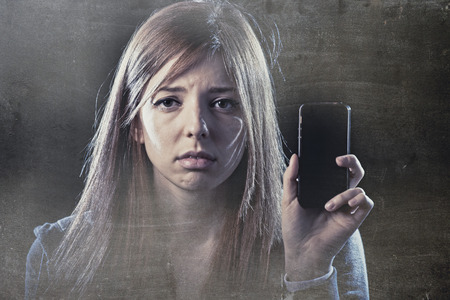 cyber bullying: young scared and worried teenager girl holding mobile phone as internet stalked victim abused and cyberbullying or cyber bullying stress concept in black background