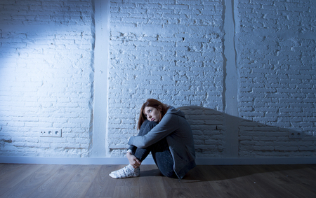 harsh: teenager girl or young woman with red hair feeling sad and scared looking overwhelmed and depressed sitting on home floor in youth depression and suffering  problem in harsh contrast light