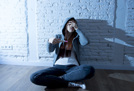 unplanned: young red hair teenager girl or young woman scared to look result after positive pregnancy test sitting on home floor worried and sad in youth unwanted maternity concept