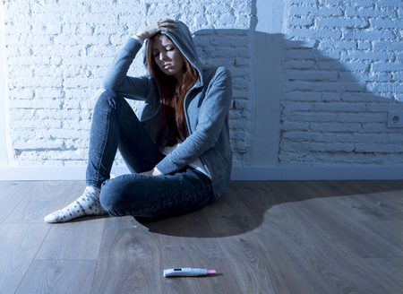 devastated: young red hair teenager girl or young woman in shock and overwhelmed after positive pregnancy test sitting on home floor devastated and depressed in youth unwanted maternity concept