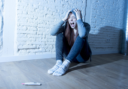 unplanned: young red hair teenager girl or young woman screaming in shock and overwhelmed after positive pregnancy test sitting on floor devastated and depressed unwanted maternity concept
